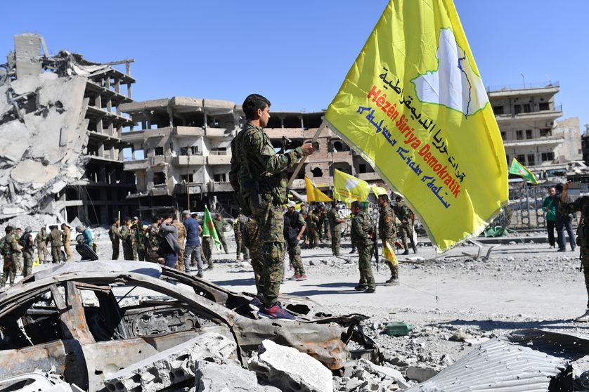 Soldats des FDS arborant leur drapeau dans les ruines de Raqqa libérée