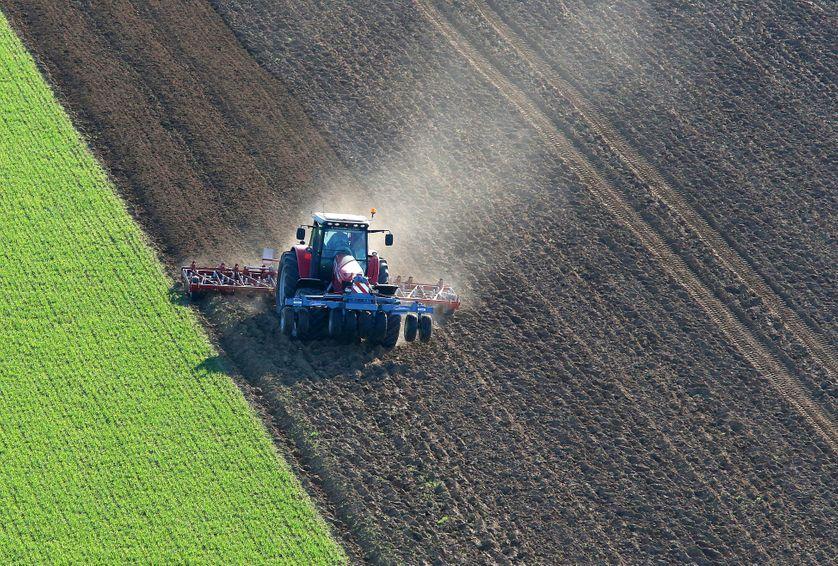 Vue aérienne montrant un tracteur semant des grains dans un champ de céréales, le 25 mars 2017, à côté de Laon, France.