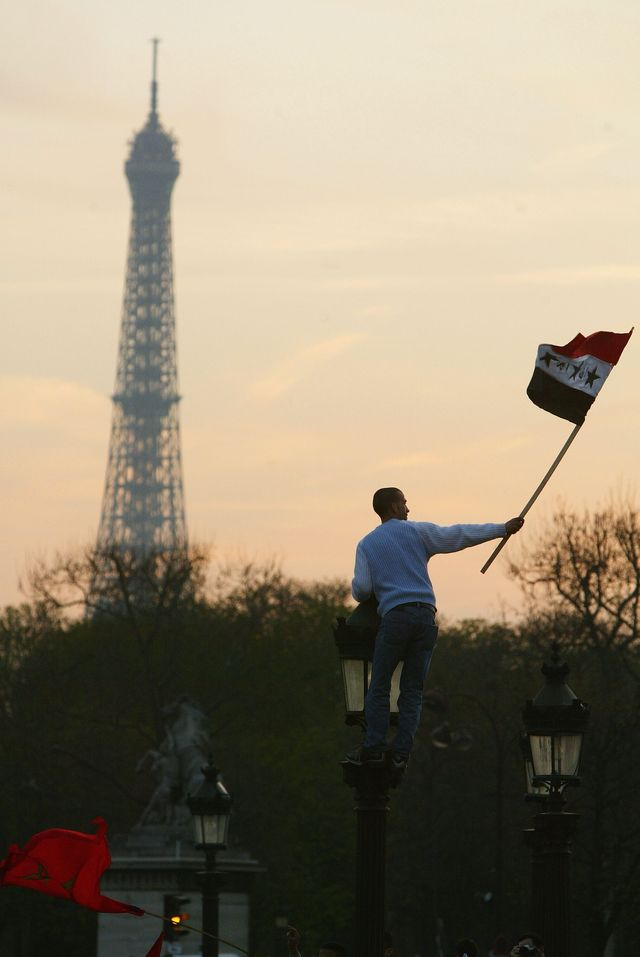 Perché sur un lampadaire, un manifestant agite un drapeau irakien lors d'un rassemblement condamnant l'action militaire contre l'Irak menée par les forces de la coalition (place de la Concorde à Paris, le 20 mars 2003)