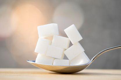 Cuillère avec neuf morceaux de sucre équivalent à la teneur en sucre d'une boisson rafraîchissante