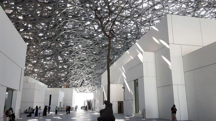 L'un des espaces extérieur du Louvre Abu Dhabi, avec le dôme dentelée et l'arbre en bronze de Giuseppe Penone.