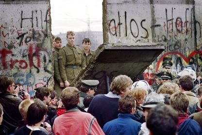Les Berlinois de l'Ouest se pressent devant le mur de Berlin au début du 11 novembre 1989, en regardant les gardes-frontières est-allemands démolir une partie du mur pour ouvrir un nouveau point de passage entre Berlin-Est et Berlin-Ouest