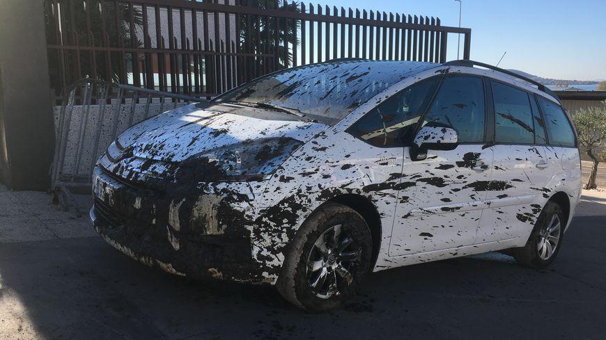 Une voiture garée dans la rue ne peut pas être déplacée, recouverte de boue toxique.