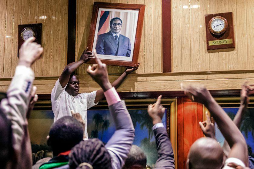 Des Zimbabwéens retirant le portrait de Robert Mugabe au Centre de conférence internationel, à l'annonce de sa démission