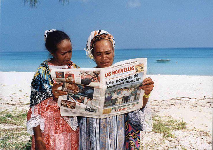 Deux femmes lisent le journal sur une plage de Nouvelle Calédonie suite à la signature de l'Accord de Nouméa, avril 1998