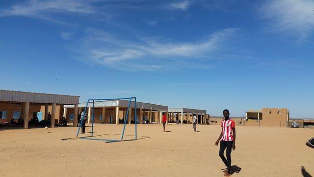 Dans la cour du centre de transit de l'OIM, des migrants jouent au football.