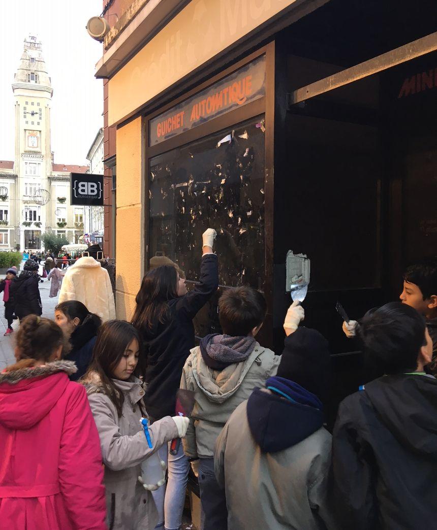 Les enfants du conseil municipal des jeunes de Privas nettoient les vitrines du centre-ville.