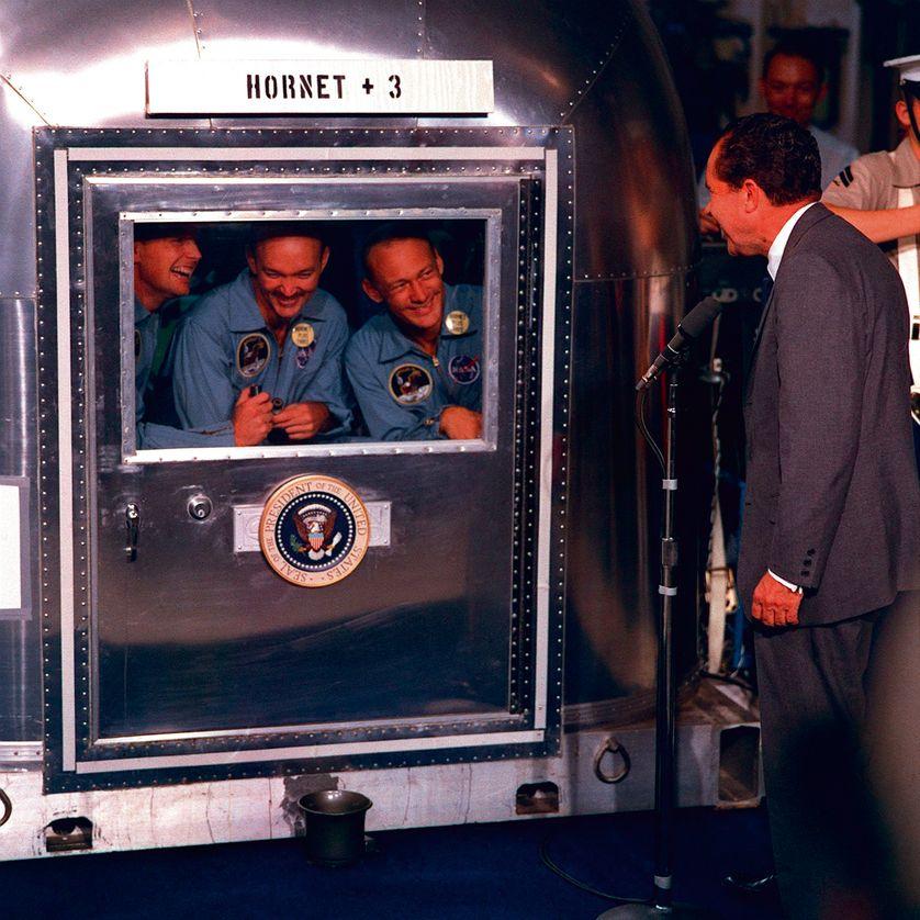 Neil A. Armstrong, Michael Collins,  et Edwin E. Aldrin, Jr., sont en quarantaine après leur mission réussie sur la Lune en juillet 69, souriants au Président Nixon.