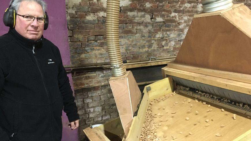 Le président de l'association Yves Saucé devant la machine à broyer les bouchons en liège