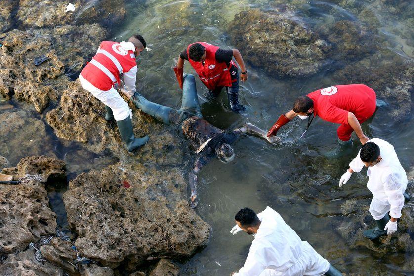 Des membres du croissant rouge libyen repêchant le corps d'un noyé, en périphérie de Tripoli, en juin 2017