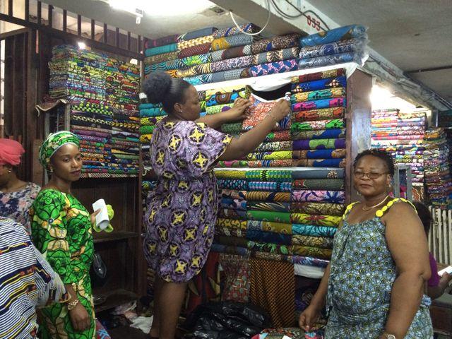 Carine Ahoundou, en vert à gauche, achète un pagne au grand marché Dantokpa, qui a un secteur réservé aux tissus.