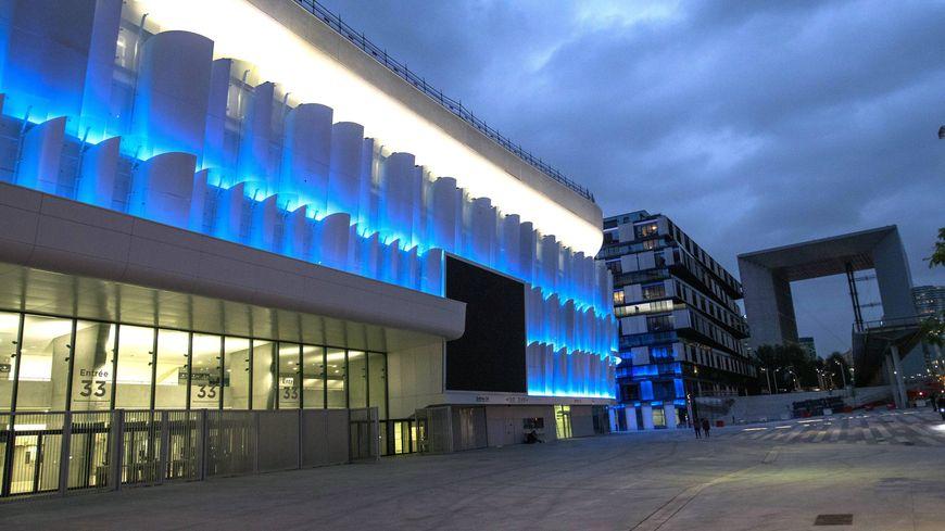 Vue extérieur de la U Arena aux couleurs du Racing 92, avec l'arche de la défense dans le fond.
