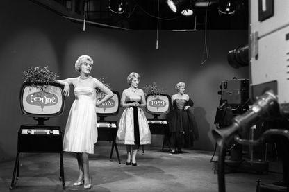 """En studio, face aux caméras, les speakerines Jacqueline Huet, Jacqueline Caurat, et Catherine Langeais, en tenue de soirée à côté de téléviseurs affichant """"bonne année 1959"""""""