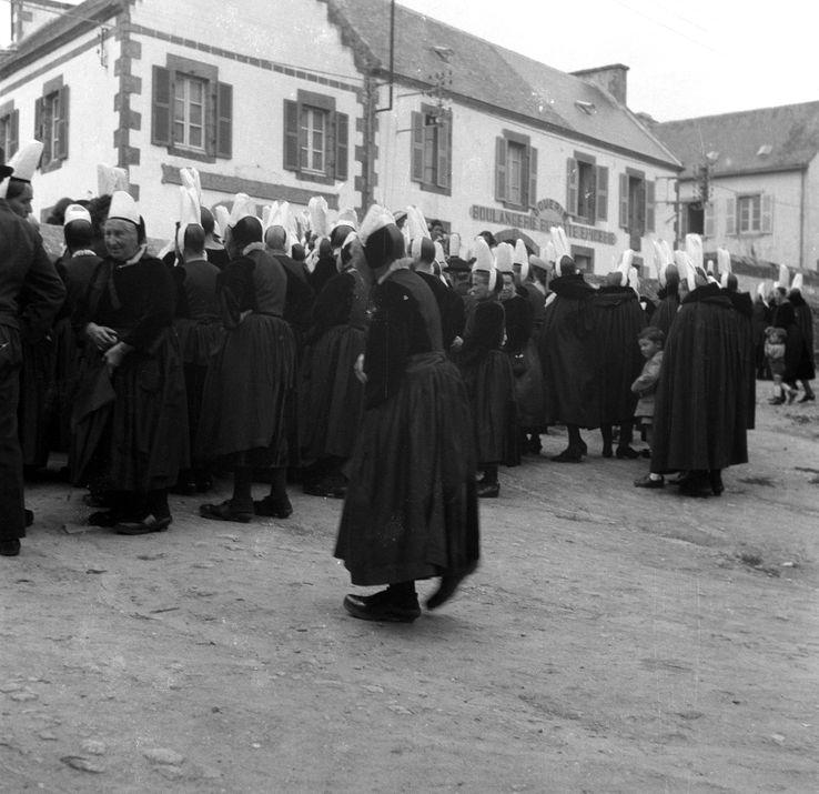 Femmes portant le bigouden et écoutant le crieur public. Prise de vue réalisée par Dan Lailler à Plozévet (Finistère).