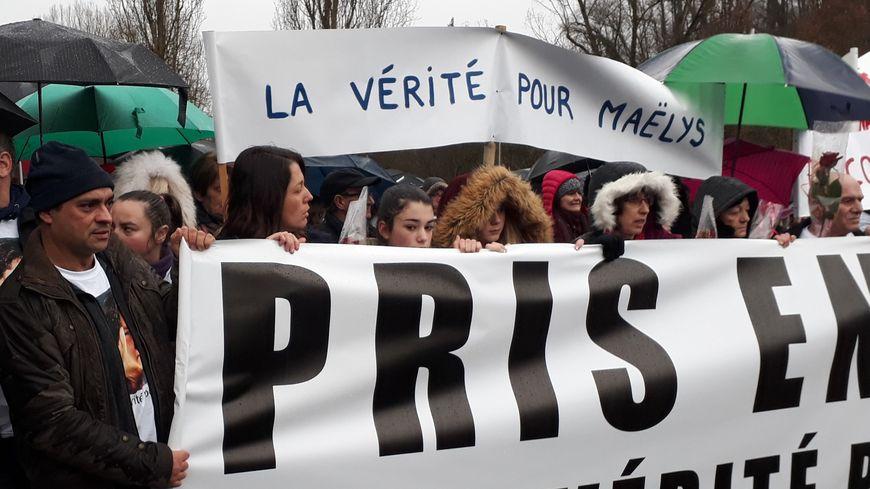 """Sur la gauche, les parents de Maelys tiennent la banderole """"Pris en otage : la vérité pour Maelys""""."""