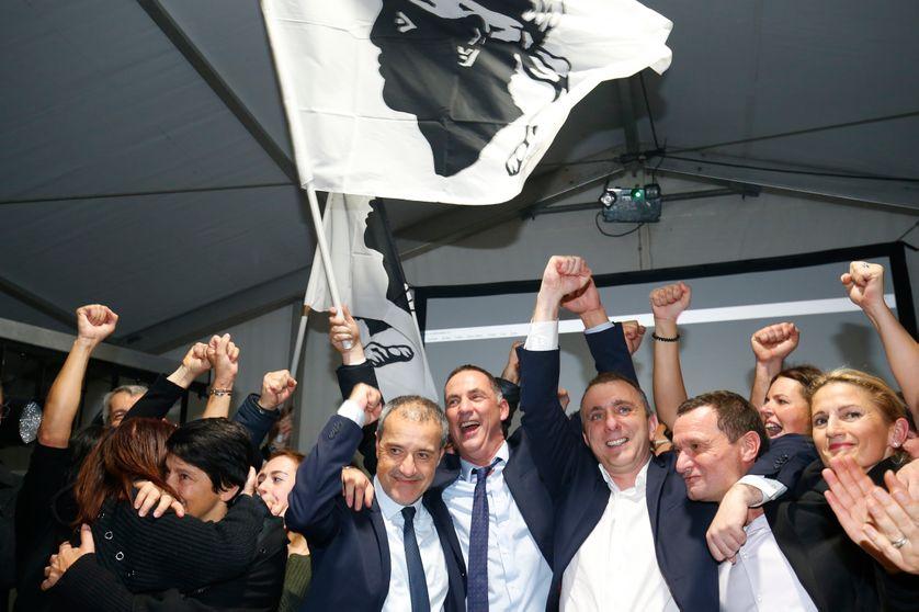 Jean Guy Talamoni et Gilles Simeoni célèbrent avec des membres de leur parti nationaliste corse les résultats de l'élection territoriale en Corse le 10 décembre 2017.
