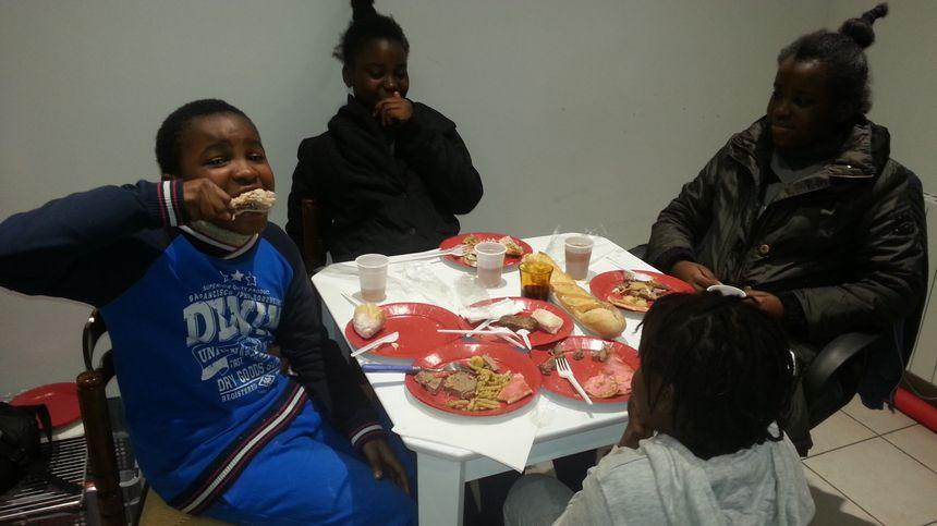 Ces enfants mordent à pleines dents ce repas qui leur est offert.  La veille, le Père Noël est venu déposer quelques jouets.