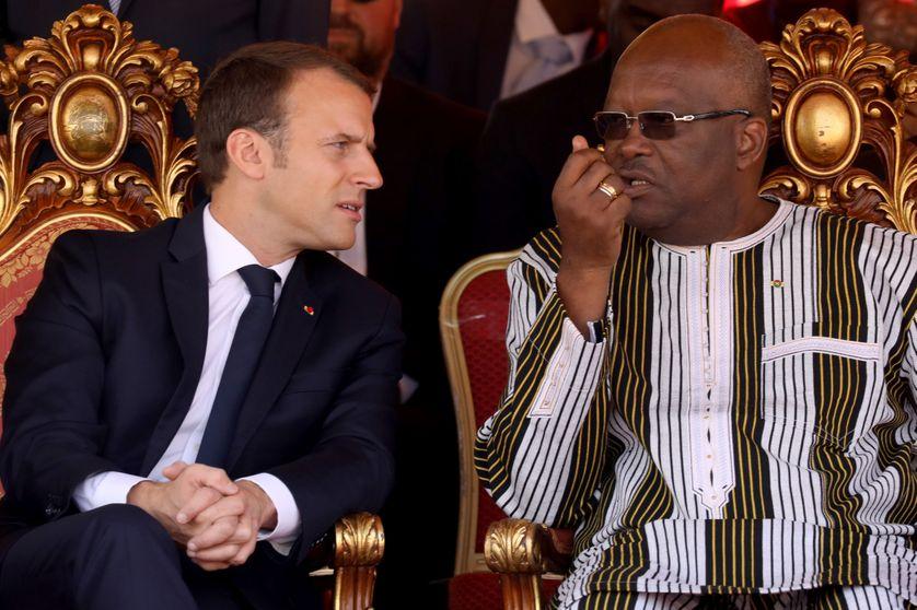 Le président français Emmanuel Macron s'entretient avec le président du Burkina Faso, Roch Marc Christian Kabore, lors de la cérémonie d'inauguration de la centrale solaire à Zaktubi, près de Ouagadougou, le 29 novembre 2017.