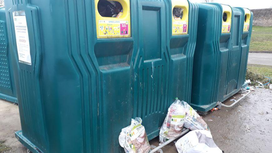 Des sacs remplis de déchets jonchent le sol au pied des conteneurs qui débordent