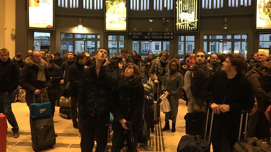 Les voyageurs les yeux rivés sur le panneau géant qui affiche les horaires de trains en gare de Caen