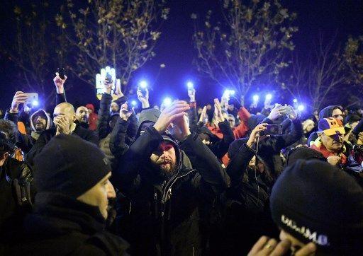 Les gens tiennent des téléphones portables allumés lors d'une manifestation devant le siège du Parlement roumain à Bucarest le 6 décembre 2017.