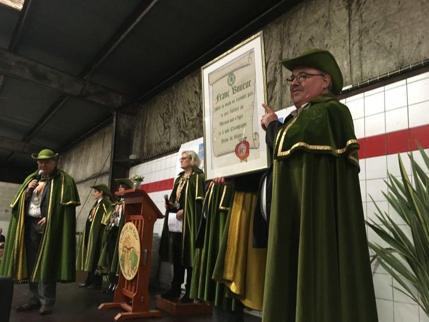 Le porteur du bâton de Saint Vincent tient le serment que les nouveaux membres doivent dire à haute voix, verre en main.