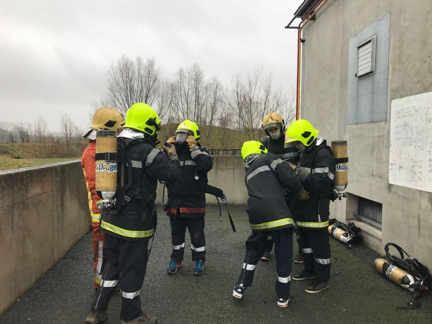 Avant d'aller éteindre un feu dans la maison, les salariés s'équipent.