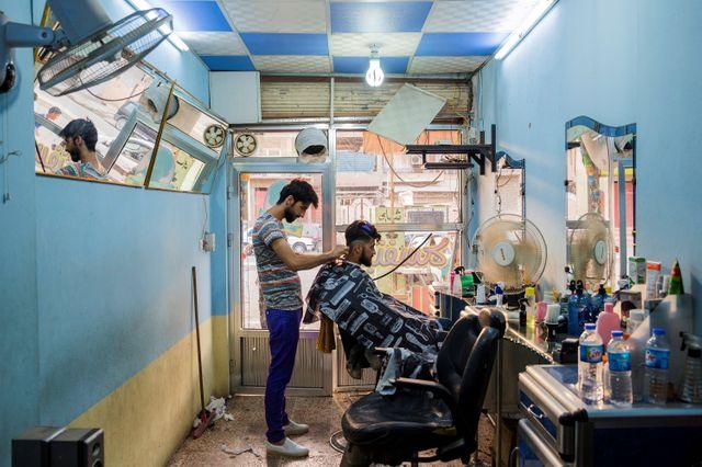 Le 02 juillet 2017. A l'est de la ville de Mossoul, les jeunes Mossouliotes expérimentent de nouvelles coupes de cheveux chez le barbier.