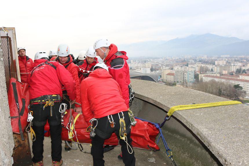 Les équipes ont récupéré le faux blessé (mais un vrai pompier du GRIMP joue ce rôle) et se préparent à le descendre en rappel par l'intérieur de la tour jusqu'en bas.