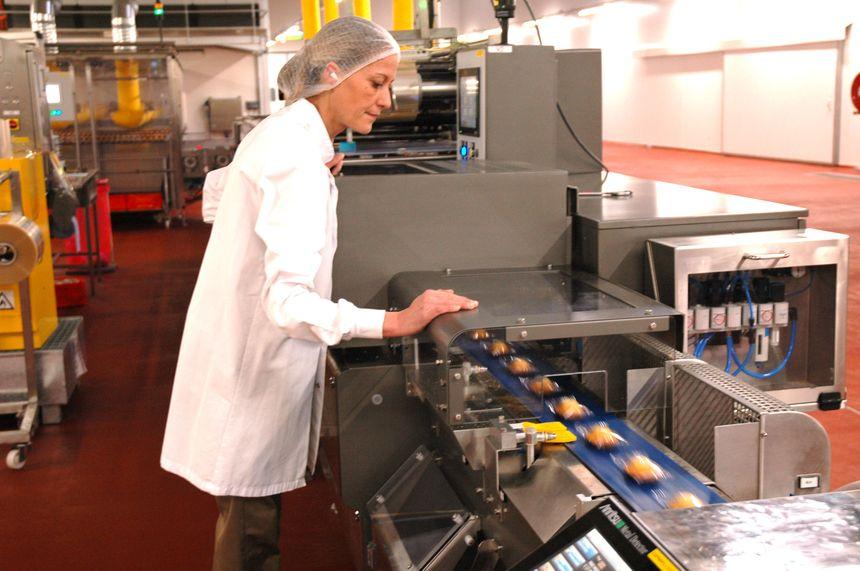 Une ouvrière contrôle le bon déroulement de l'emballage des madeleines.