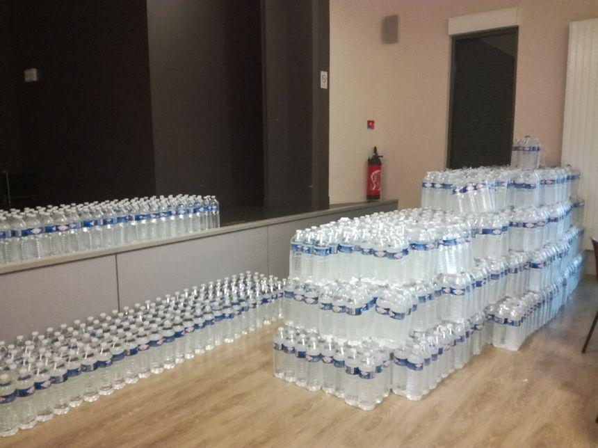 Les bouteilles à distribuer sont dans la salle des fêtes de Cailly