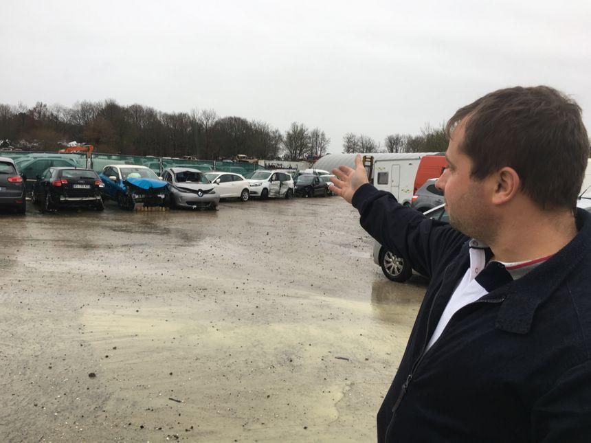 Guillaume Augustin montre l'endroit, derrière les voitures, où étaient installés les anciens locaux partis en fumée dans l'incendie.
