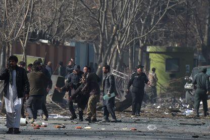 Des volontaires afghans et des policiers aident les blessés sur les lieux de l'explosion à la voiture piégée devant l'ancien bâtiment du ministère de l'Intérieur à Kaboul le 27 janvier 2018.