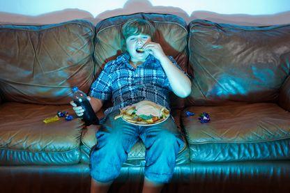 Enfant mangeant devant son écran