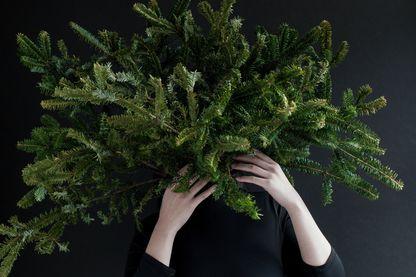 Femme tenant des branches d'arbre de pin sur fond noir.
