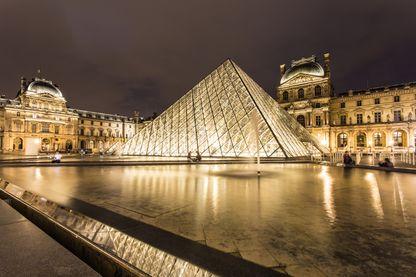 Le Louvre et sa pyramide de verre la nuit à Paris