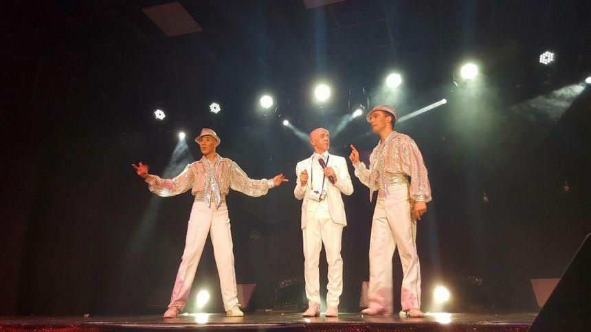 Loïc, chanteur et homme-orchestre du spectacle avec deux des danseurs de la troupe.