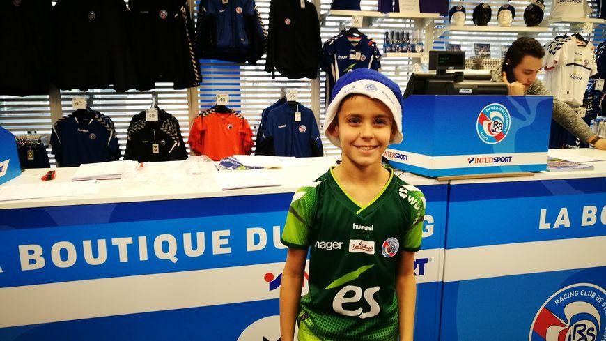 Romain, 10 ans, pose fièrement avec son maillot du RCSA