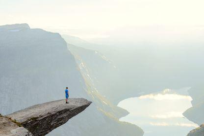 Voyageur debout sur Trolltunga à Odda, comté de Hordaland, Norvège