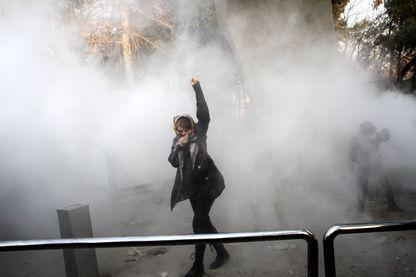 Une femme iranienne lève le poing au milieu des gaz lacrymogènes à l'université de Téhéran