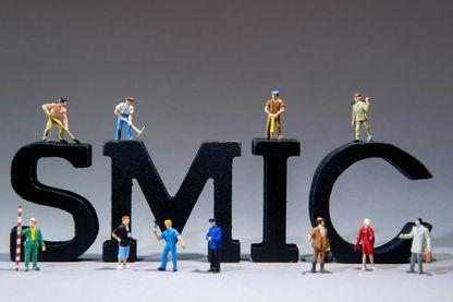 """Une photo prise le 4 décembre 2015 à Lille montre des figurines de travailleurs autour de l'acronyme SMIC """"Salaire minimum de croissance - salaire minimum légal"""""""