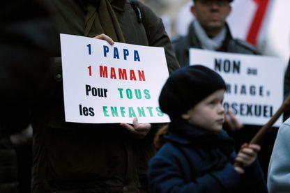 """Un homme tient une pancarte """"Un papa, une maman, pour tous les enfants"""" lors d'une manifestation contre le mariage homosexuel le 4 avril 2013"""