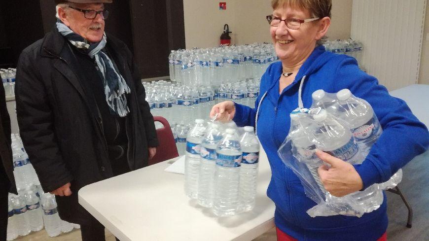 A Cailly, Maryse vient chercher des packs d'eau à la salle des fêtes.