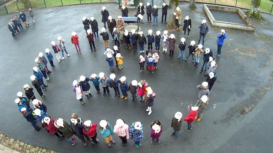 """Les 60 élèves de l'école ont formé un """"un-smiley"""", un bonhomme mécontent, dans la cour de l'école."""