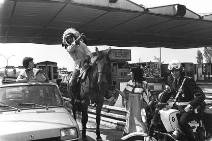 """Photo prise le 28 juin 1977 sur une autoroute française d'un homme à cheval déguisé en Indien donnant des indications à une automobiliste, lors d'une opération de """"Bison Futé"""" de distribution de cartes routières. AFP"""