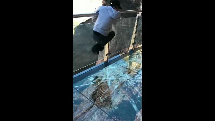 Le garçon sur le pont en verre est pris de panique