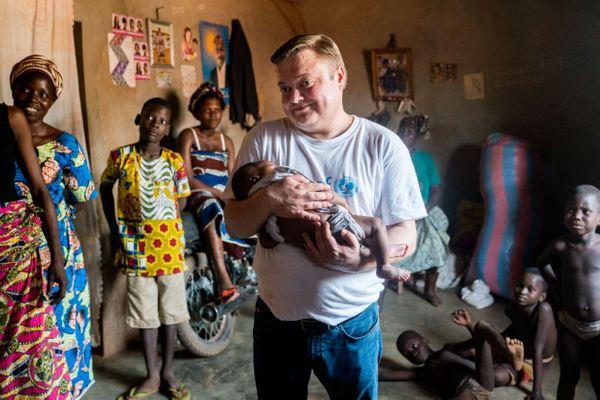 Mikko Franck dans le village de Houagon avec dans les bras Bellevie, nourrisson d'un mois suivi par la communauté du centre de santé local