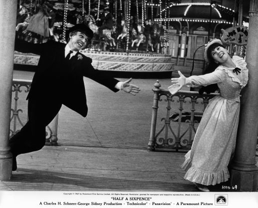 ommy Steele and Julia Foster reaching out to each other in a scene from the film 'Half A Sixpence', 1967