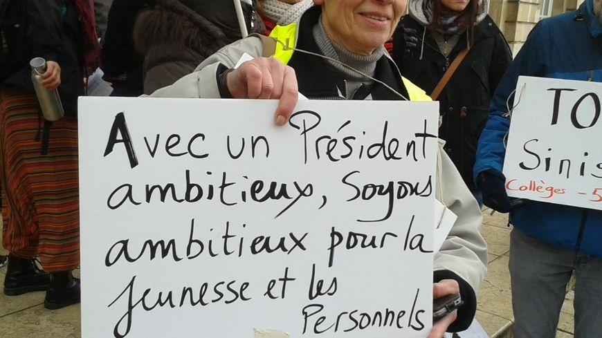 L'ambition exprimée par le chef de l'Etat pour l'Education nationale contredit la réalité, selon les manifestants, comme cette enseignante de Toul le suggère avec cette pancarte..