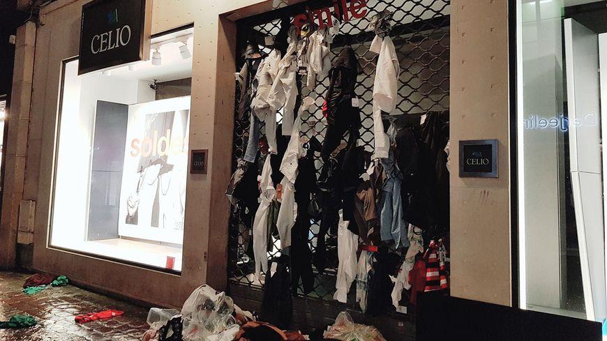 Des vêtements en lambeaux retrouvés dans une poubelle devant la boutique accrochés sur les grilles par des passants.